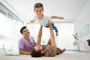 Male,Gay,Couple,Playing,With,Foster,Son.,Adoption,Concept